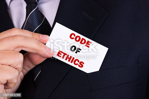 531925785 istock photo Businessman putting a card with text code of ethics in the pocket 1207453265