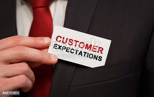 istock Businessman putting a card with text Customer Expectations in the pocket 848701624