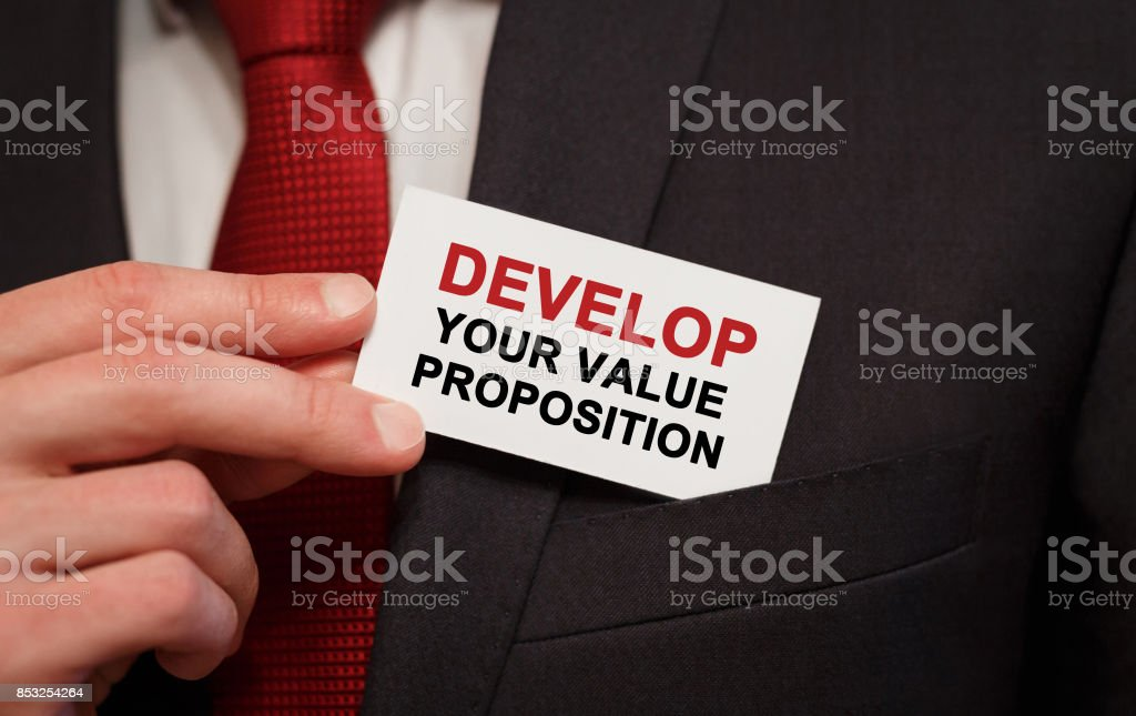 Businessman putting a card with text Develop Your Value Proposition in the pocket stock photo