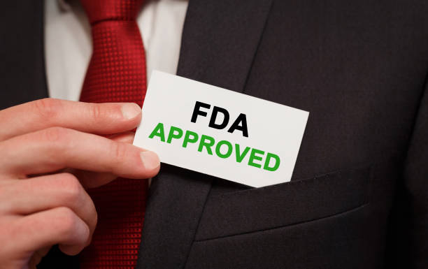 businessman putting a card with text fda approved in the pocket - fda stock photos and pictures