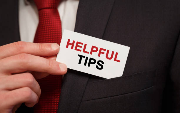 Businessman putting a card with text Helpful tips in the pocket stock photo