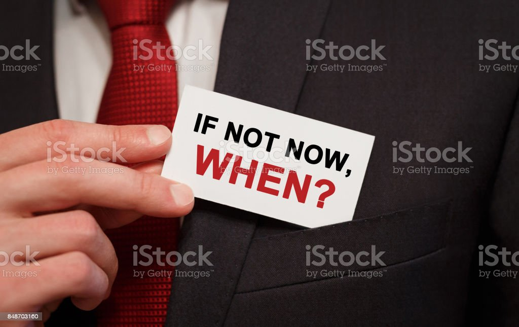 Businessman putting a card with text if not now, when in the pocket stock photo