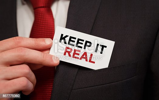 Businessman putting a card with text Keep It Real in the pocket