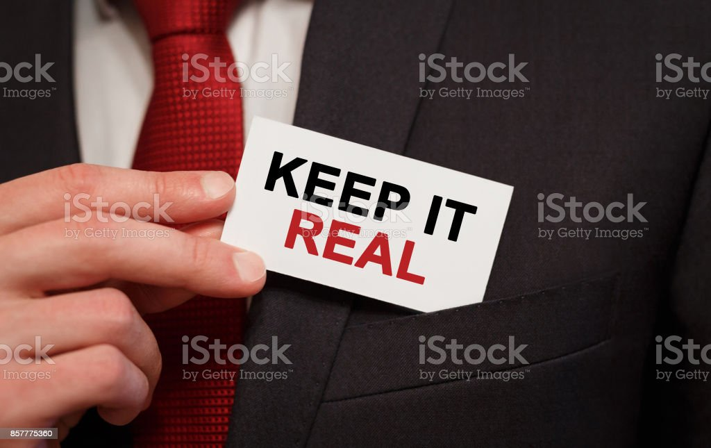 Businessman putting a card with text Keep It Real in the pocket stock photo