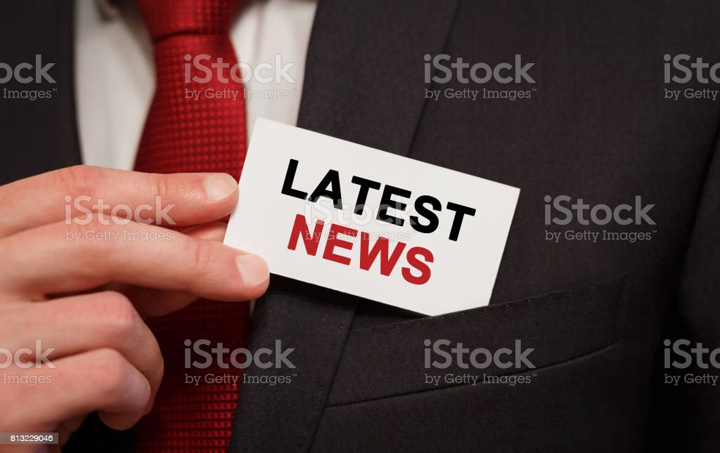 Businessman putting a card with text Latest News in the pocket stock photo