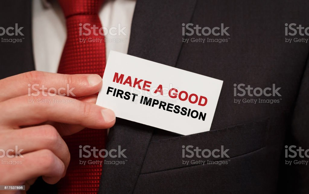 Businessman putting a card with text Make a good first impression in the pocket stock photo