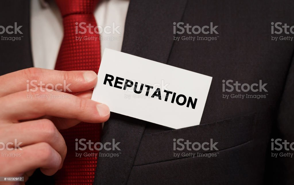 Businessman putting a card with text Reputation in the pocket stock photo
