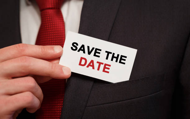 businessman putting a card with text save the date in the pocket - calendar date stock photos and pictures