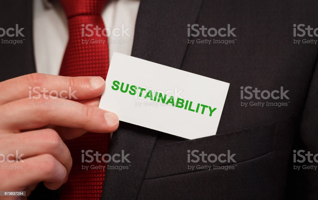 Businessman putting a card with text Sustainability in the pocket stock photo