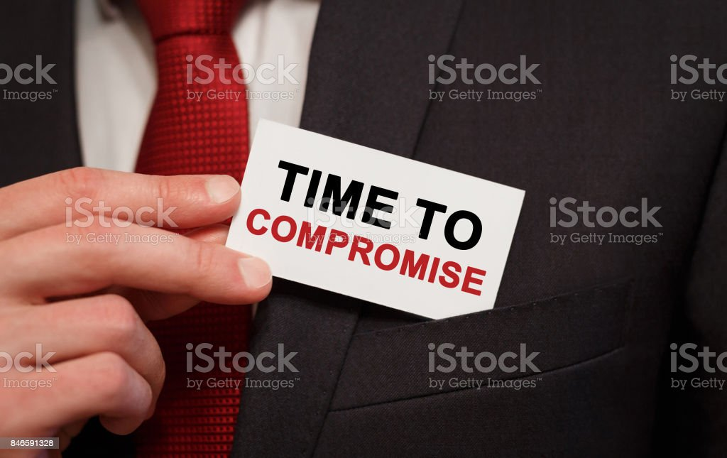 Businessman putting a card with text Time to compromise in the pocket stock photo