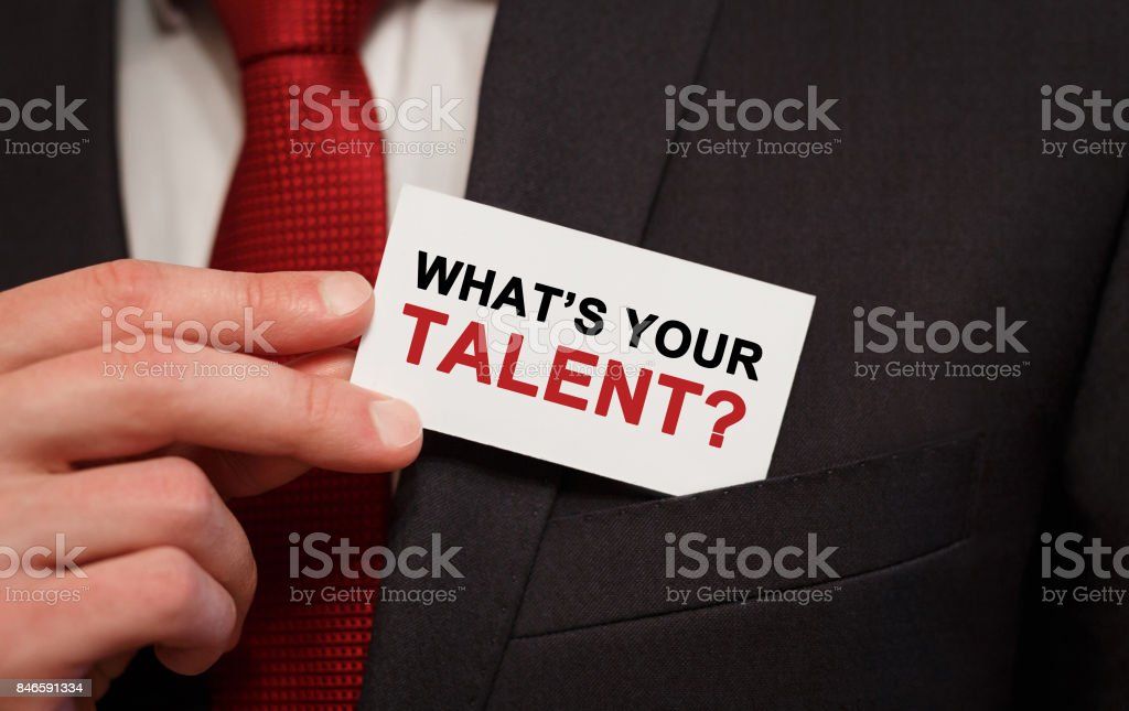 Businessman putting a card with text Whats Your Talent in the pocket stock photo