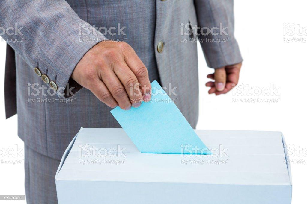 Homme d'affaires, mettre le bulletin dans la boîte de vote photo libre de droits