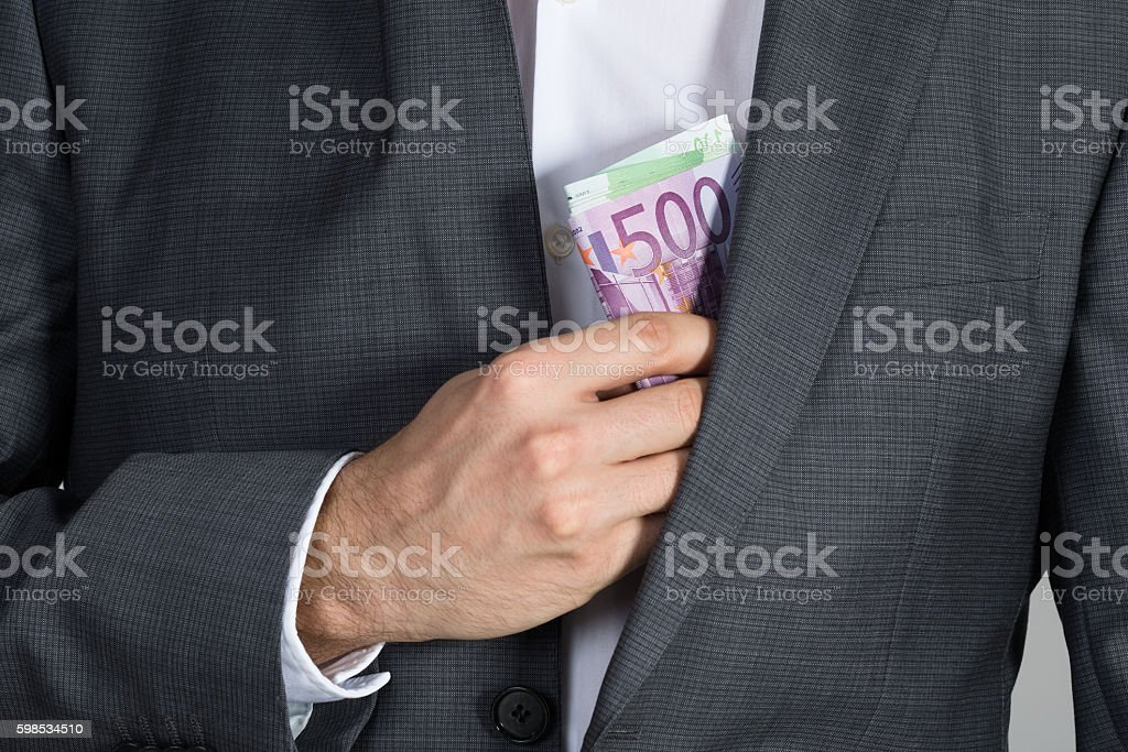 Businessman Putting Bribe In Suit Pocket photo libre de droits