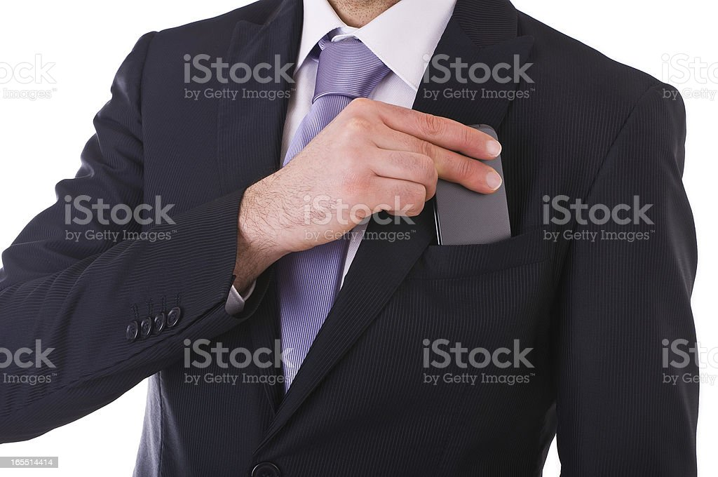 Businessman putting cellphone into pocket. stock photo