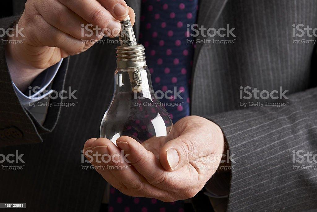 Businessman Putting Dollar Bill Into Light Bulb stock photo