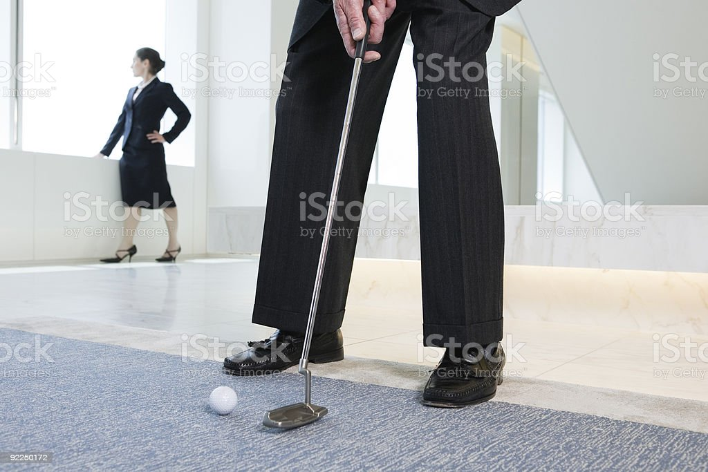 Businessman putting golf ball with woman executive in background royalty-free stock photo