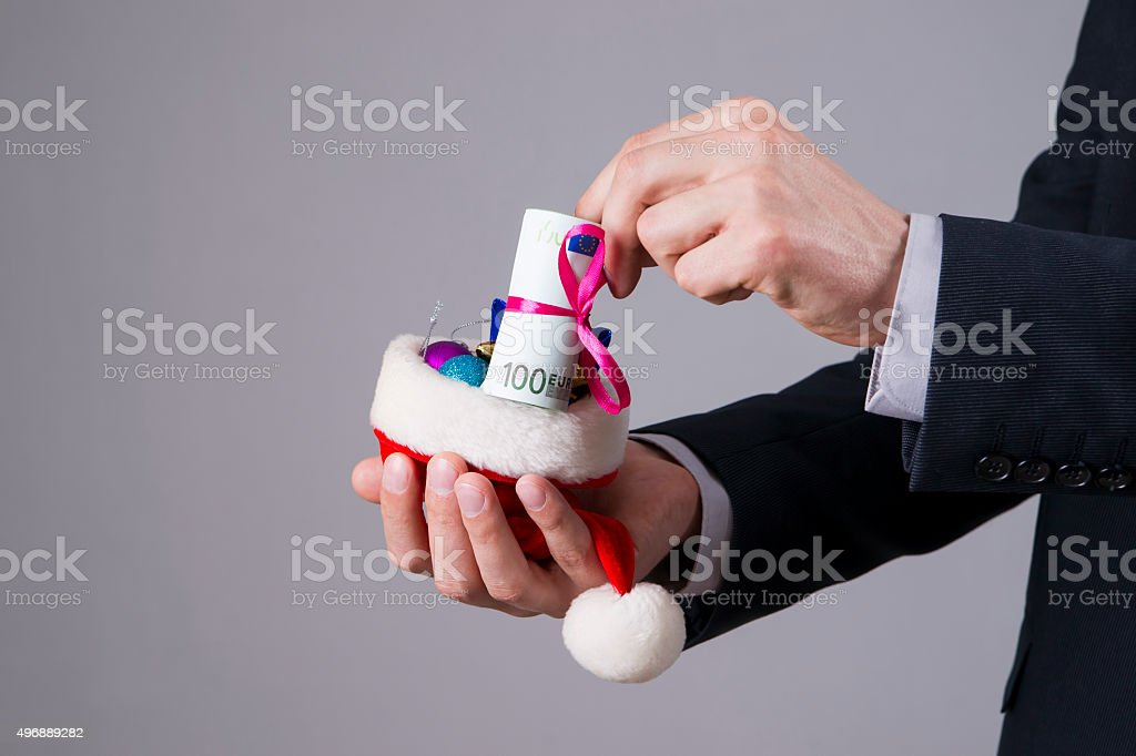 Businessman putting money in a Santa hat stock photo