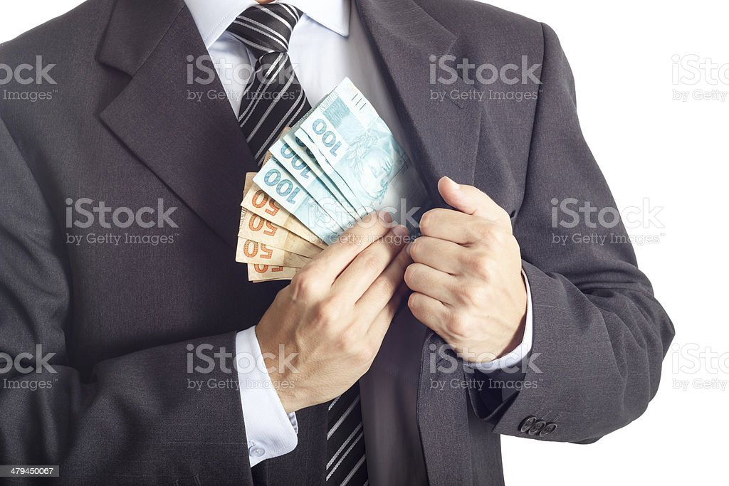 Businessman putting money in his pocket stock photo