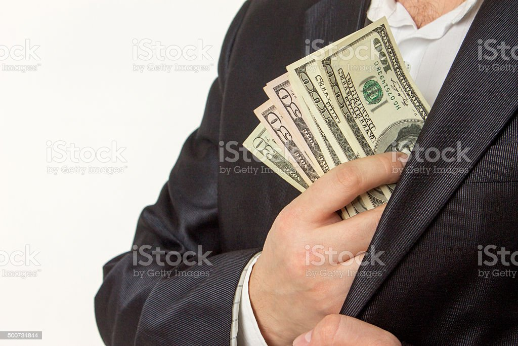 Businessman putting money in suit jacket pocket stock photo