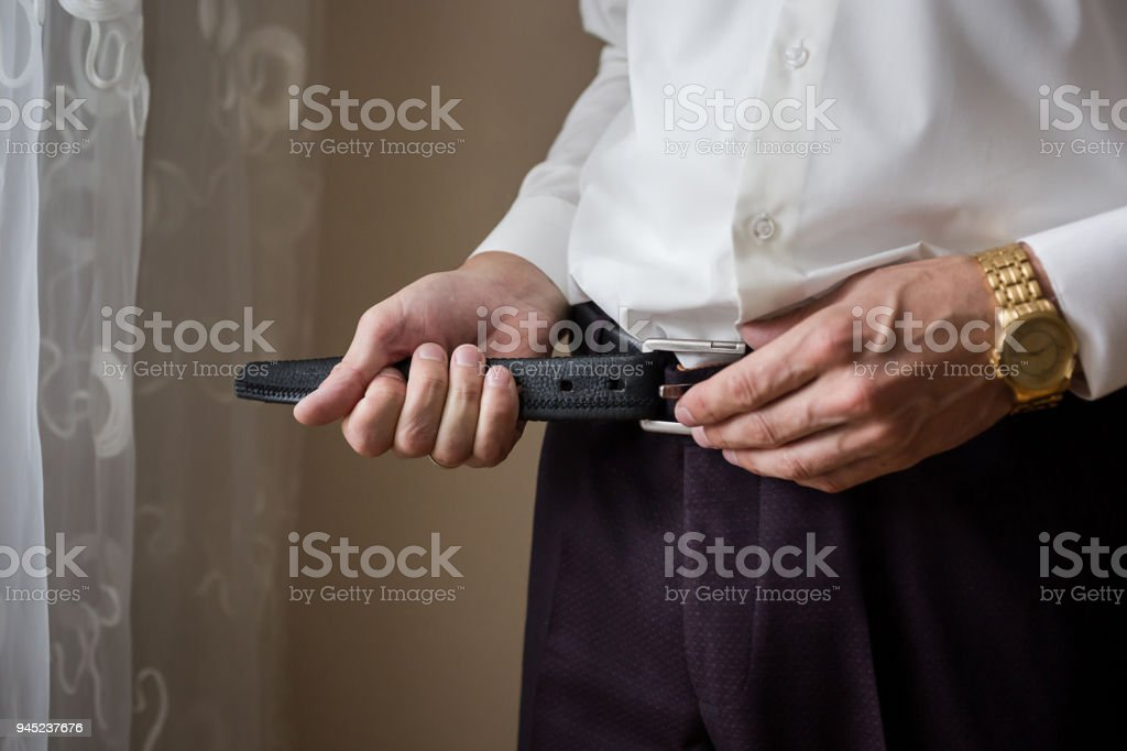 Businessman putting on a belt, fashion and clothing concept,groom getting ready in the morning before ceremony stock photo