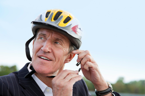 Businessman putting on bicycle helmet