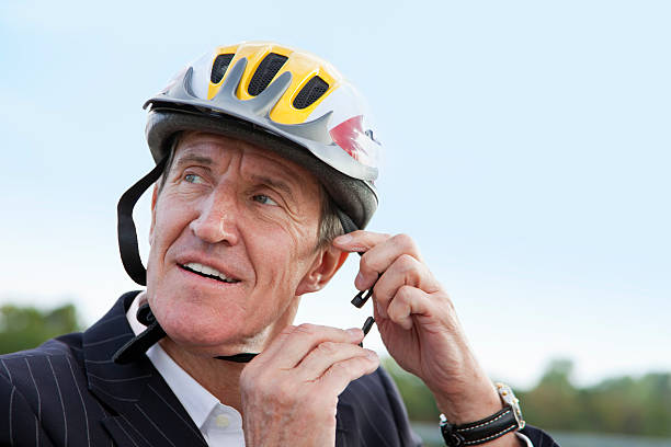 geschäftsmann beim auf fahrrad helm - arbeit in münchen stock-fotos und bilder