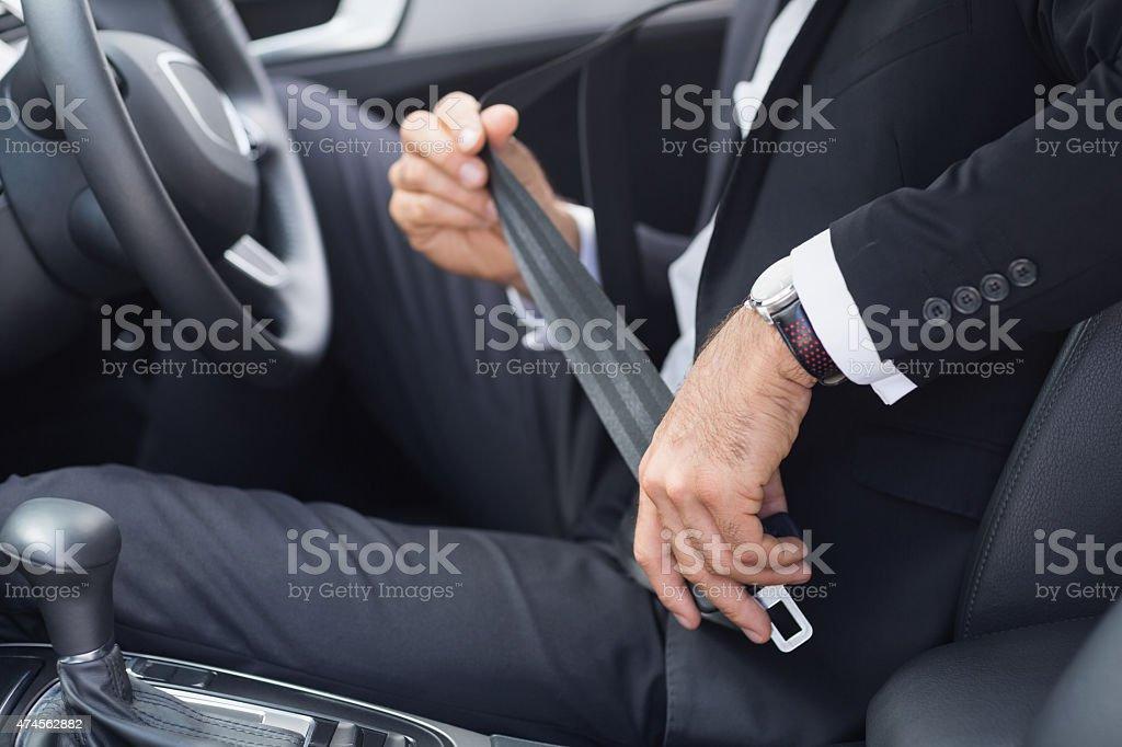 Businessman putting on his seat belt stock photo