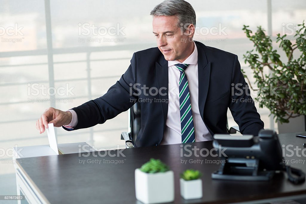 Businessman putting paper into drawer stock photo