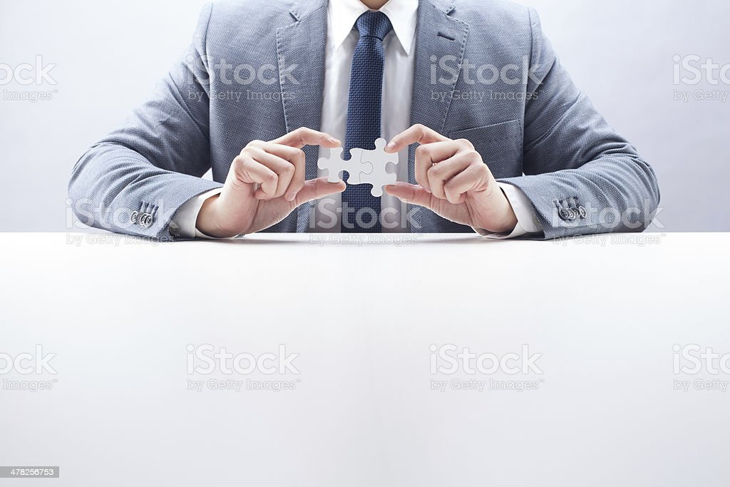 Businessman Putting Puzzles Together royalty-free stock photo