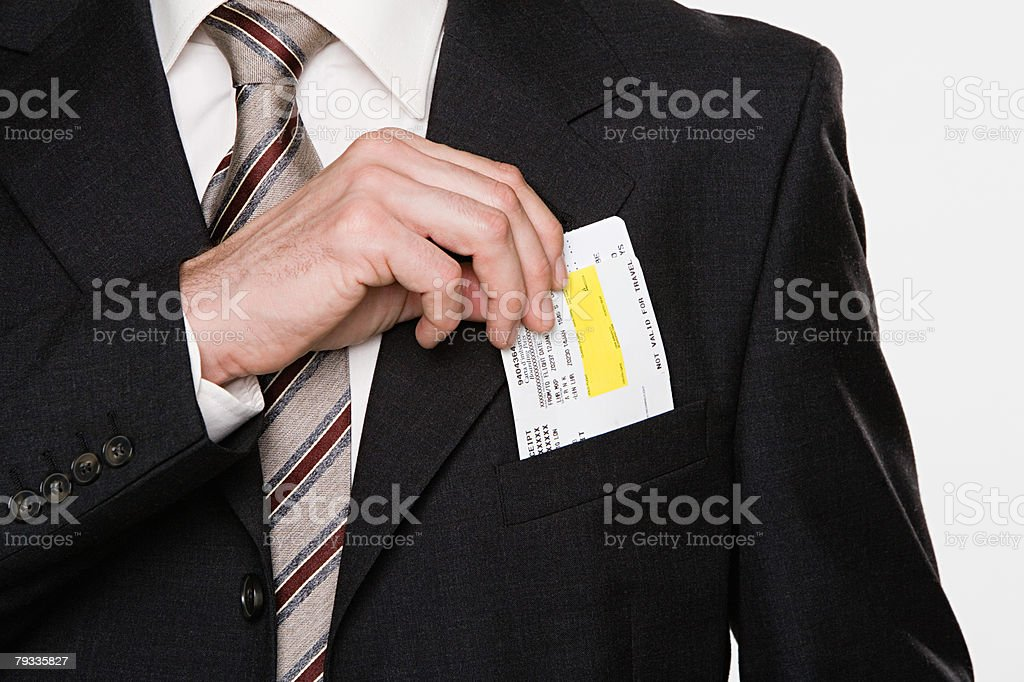 Businessman putting tickets in his pocket stock photo