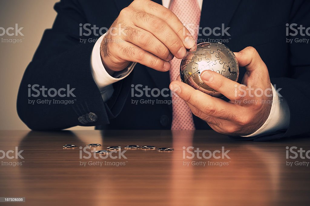 Businessman putting together jigsaw puzzle stock photo