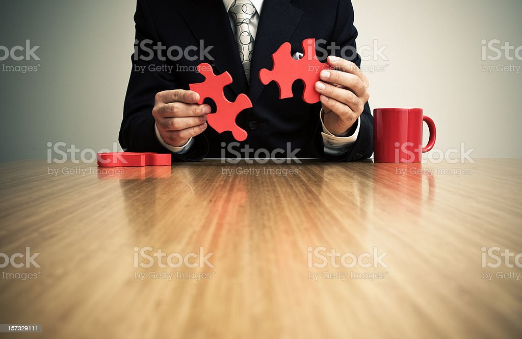 Businessman putting together jigsaw puzzle royalty-free stock photo