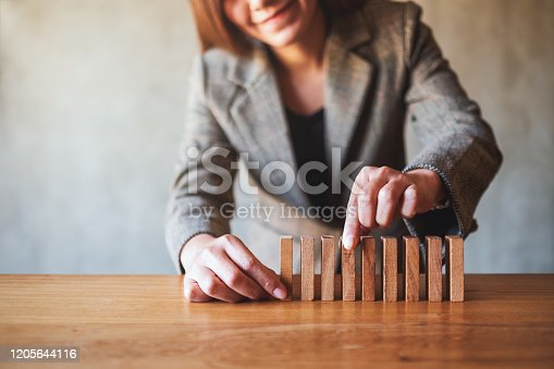 istock businessman putting wooden block in a row on the table for business concept 1205644116