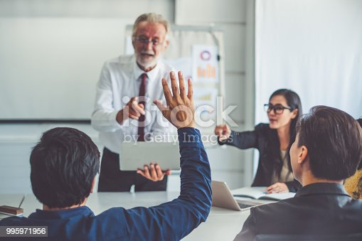 Businessman raising hand for asking speaker for question and answer concept in meeting room of diversity business people