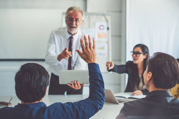 businessman raising hand for asking speaker for question and answer concept in meeting room of diversity business people - training imagens e fotografias de stock