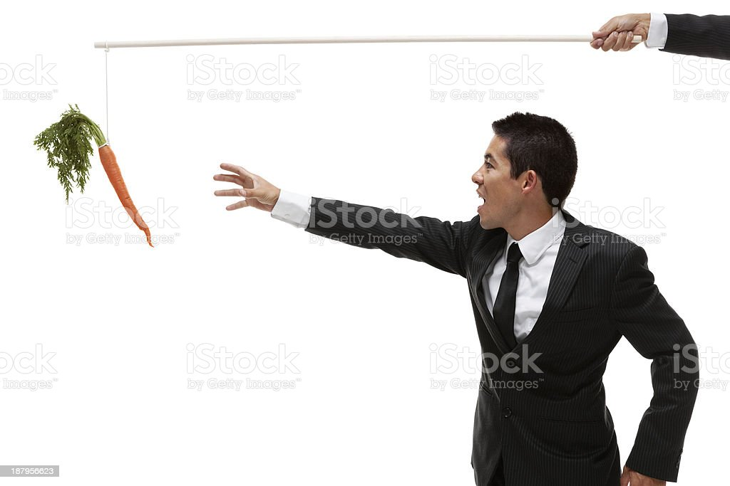Businessman reaching for carrot on a stick stock photo