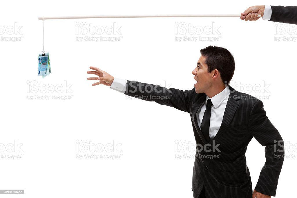 Businessman reaching for euros hanging from a stick stock photo