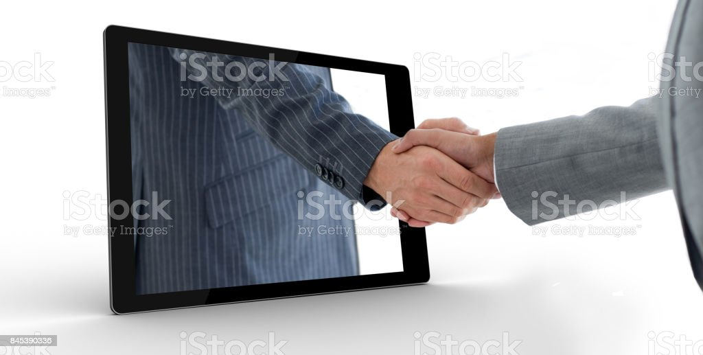 Businessman reaching out from tablet and shaking hands stock photo