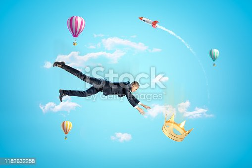 1035636416 istock photo Businessman reaching to golden crown with hot air balloons and silver red space rocket in the air on blue background 1182632258