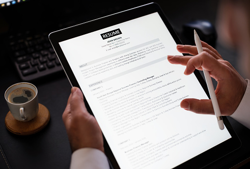 Businessman Reading A Resume On Digital Tablet To Hire Correct Personnel
