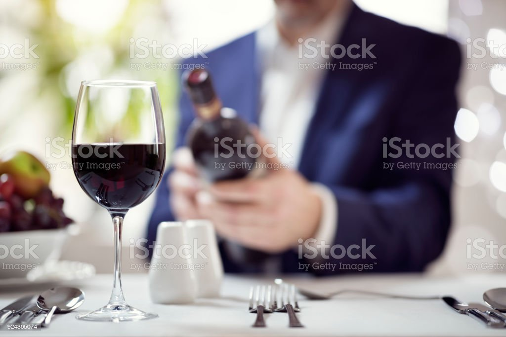 Businessman reading a wine bottle label in restaurant stock photo