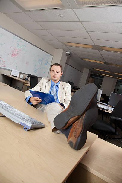 Businessman reading at desk stock photo