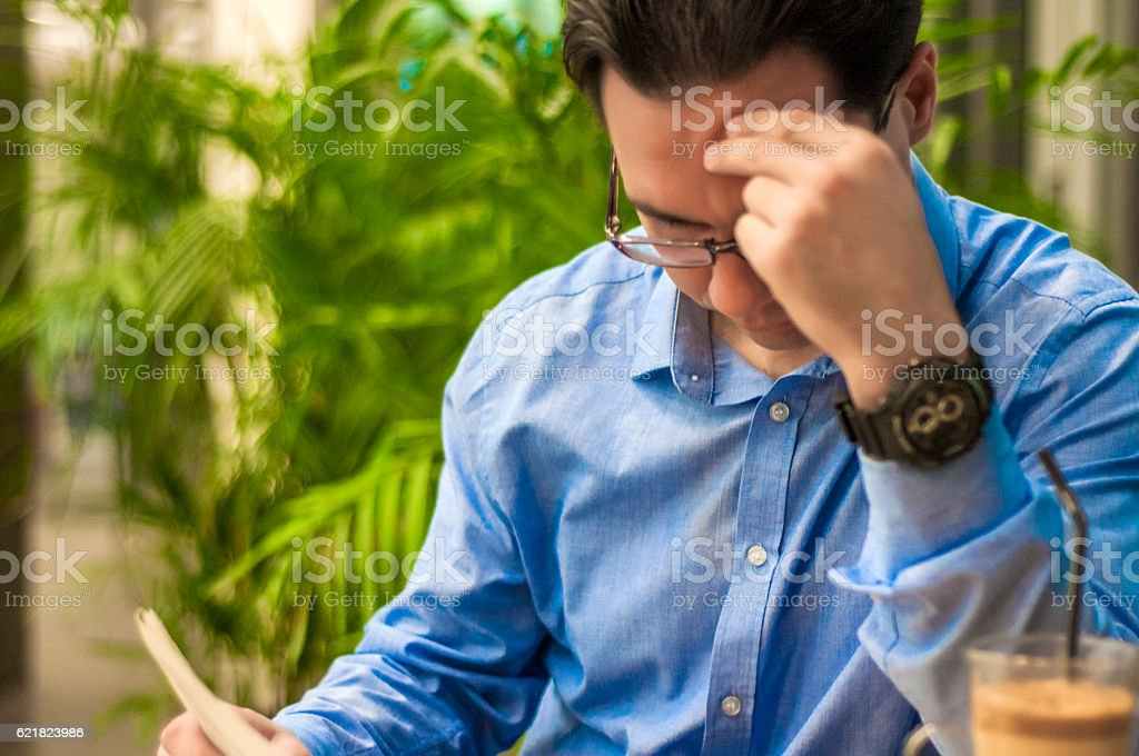 Businessman reading bad breaking news on a financial newspaper stock photo
