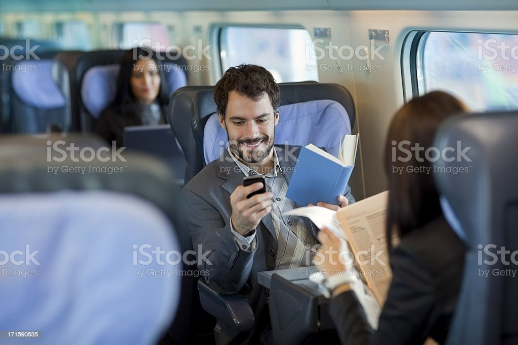 Businessman reading  book  on Train and using mobile phone stock photo