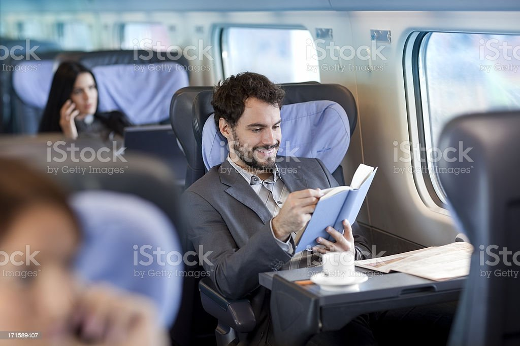 Businessman reading  book  on Train royalty-free stock photo