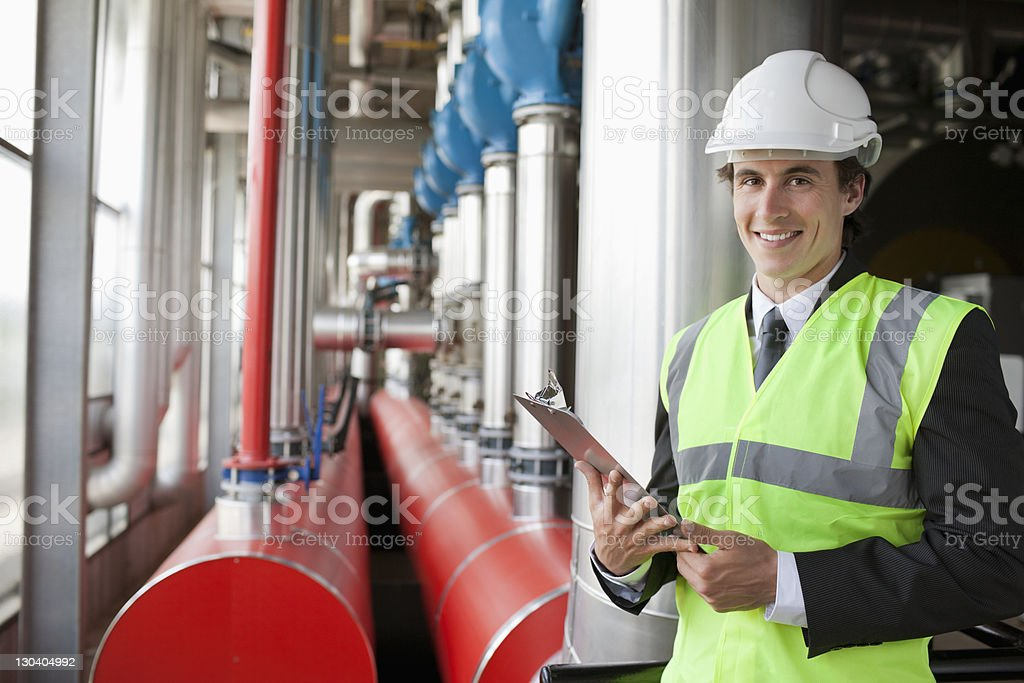 Businessman reading clipboard in factory royalty-free stock photo