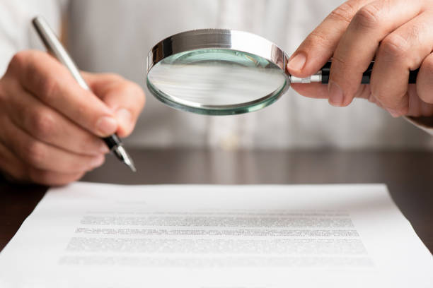 Businessman Reading Contract Carefully Using Magnifying Glass Before Signing stock photo