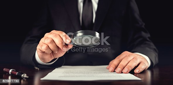 istock Businessman Reading Contract Details Before Signing 825677730