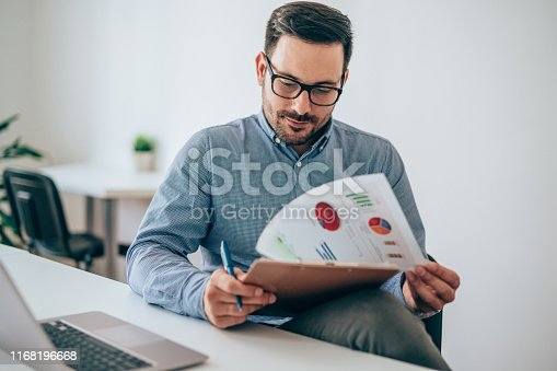 istock Businessman reading document at desk in office 1168196668