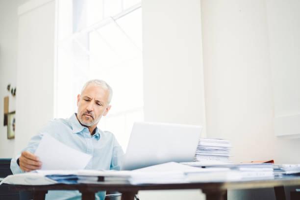 geschäftsmann lesen von dokumenten am schreibtisch in büro - schreibtischunterlagen stock-fotos und bilder